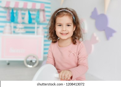 Cute little baby girl dark brunette curly lady hair funny child birthday party fun children room decoration candy bar sweet play toy wear style clothes dress.