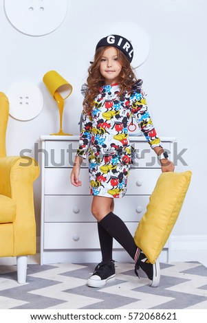 c6fa051ea Cute little baby girl fashion pretty model dark blonde curly lady hair  funny child birthday party fun children room yellow chair interior play  pillow fight ...