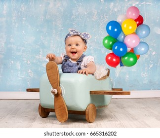 cute Little Baby Girl flying on wooden airplane with colorful balloons