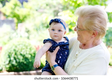 Cute little baby girl with grandmother on summer day in garden