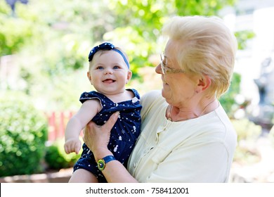 Cute little baby girl with grandmother on summer day in garden. Happy senior woman holding smiling child on arm.