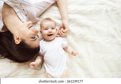 Cute little baby girl and her mother lying on a knitted blanket.