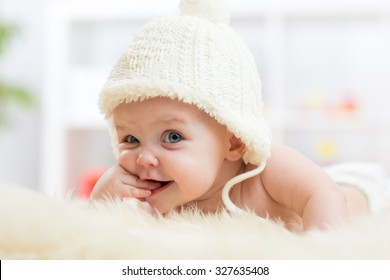 Cute little baby girl looking into the camera and weared in white hat.