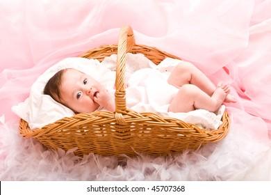 Cute little baby girl lying in the basket