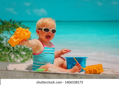 cute little baby girl play with toys on beach