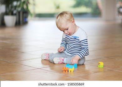 Cute little baby girl play with plastic bricks sitting indoors on a tiles floor
