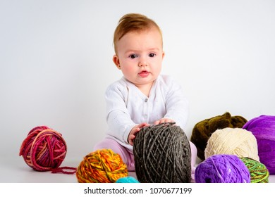 Cute little baby girl playin with colorful wool balls on a white backdrop