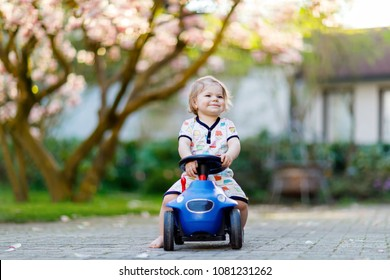 Cute little baby girl playing with blue small toy car in garden of home or nursery. Adorable beautiful toddler child with blossoming magnolia on background