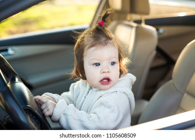 A cute little baby girl is playing and having fun in the car while driving. Happy, carefree childhood