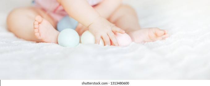 Cute little baby girl, playing with colorful easter eggs in pink clothes, sitting on bed in living room, babygirl smiling happily