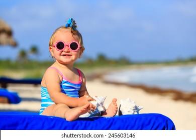cute little baby girl with seashells on tropical sand beach