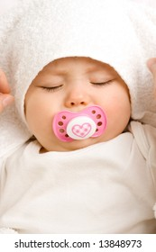 A cute little baby girl sleeping with a dummy in her mouth.