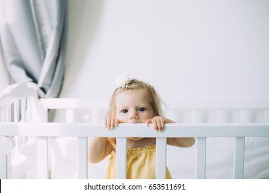 Cute little baby girl standing in the crib and looking into the camera
