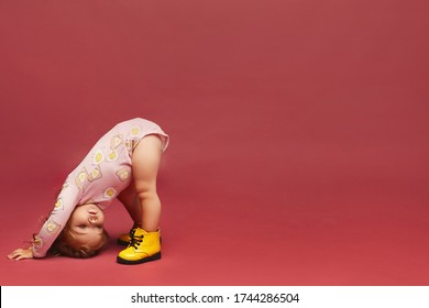 A cute little baby girl in stylish pink outfit and yellow boots is standing on the head on the pink background, isolated with copy space. Kids fashion