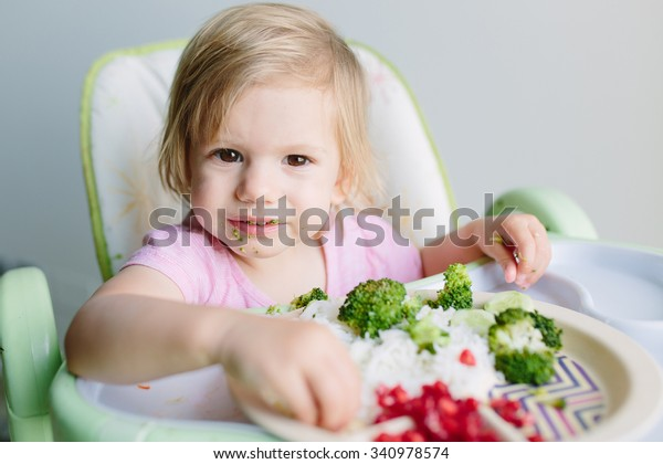 Cute little baby girl toddler eating her lunch of rice, broccoli and pomegranate indoors