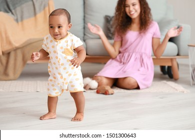 Cute little baby learning to walk at home