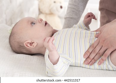 Cute little baby looking at his young mother with big eyes. Baby lying on a changing table, mother's hand on kid's belly