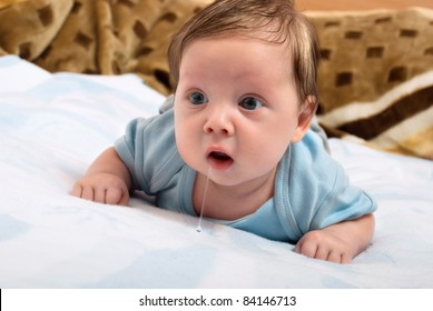 Cute little baby looks into the camera and drooling while lying on the bed. Creative concept photos