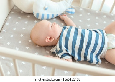 Cute little baby lying in crib. Sleeping time