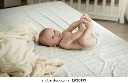 Cute little baby lying on bed and holding feet