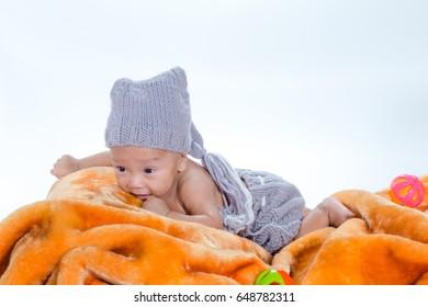 Cute little baby lying on a blanket in nursery.