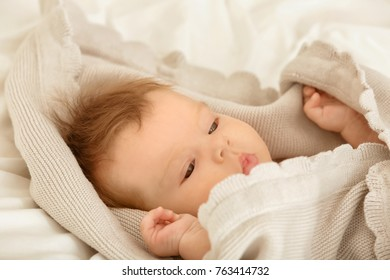 Cute little baby lying on bed at home