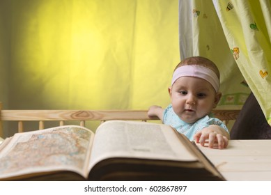 Cute little baby next to a big old book