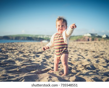 A cute little baby on the beach is pointing, focus on his finger