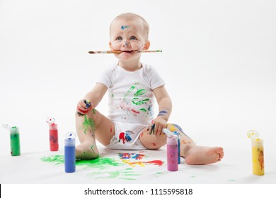Cute little baby painting with paintbrush and colorful paints on white background. Brush in the mouth.