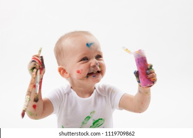 Cute little baby painting with paintbrush and colorful paints on white background