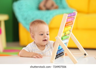 Cute little baby playing with abacus at home