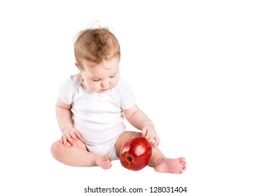 Cute little baby playing with a big red apple, isolated on white
