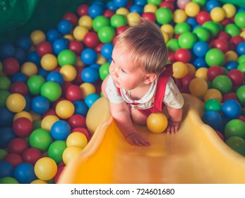 A cute little baby is playing in a pool of balls