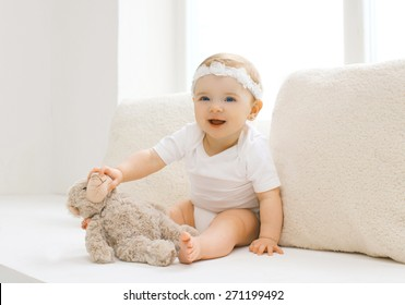 Cute little baby playing with toy at home in white room near window