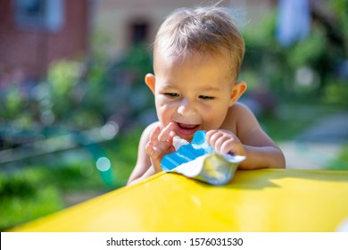 cute little baby put his finger in the package of fruit puree in pouch  in front of the yellow table. on the background is a green garden on a sunny day in blur, close up