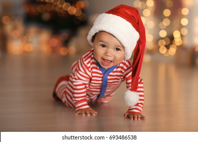 Cute little baby with Santa hat on floor and blurred Christmas lights on background