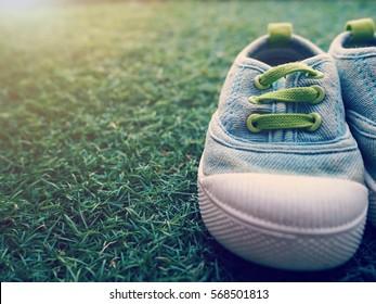 A cute little baby shoe on green lawn