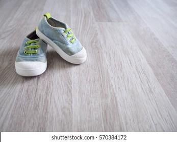 Cute little baby shoe on wood floor