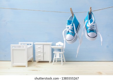 Cute little baby shoes hanghang on rope in baby room background