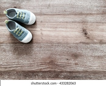 Cute little baby shoes on wood background , top view
