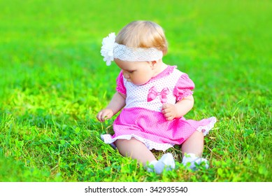 Cute little baby sitting on grass in summer day