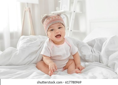Cute little baby sitting on bed at home