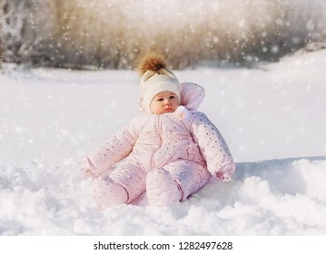 Cute little baby sitting in white snow wearing a warm jacket and knitted hat. Little girl in snow - Image