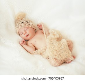 Cute little baby is  sleeping in a gentle knitted blanket of cream color