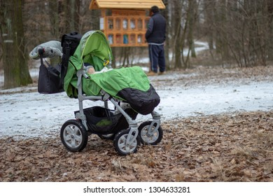 cute little baby is sleeping in the green stroller which is standing on the snowy ground with young man in the background in the forest in winter