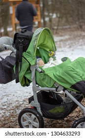 cute little baby is sleeping in the green stroller which is standing on the snowy ground