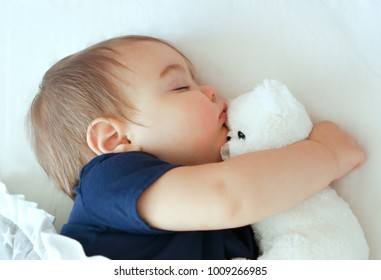 Cute little baby sleeping and hugging white teddy bear, close-up