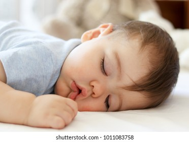 Cute little baby sleeping on stomach with funny open mouth. Daytime sleeping. Close-up.