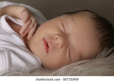 Cute little baby sleeping on soft plaid, closeup