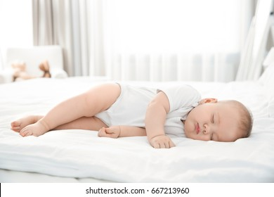Cute little baby sleeping on bed at home
